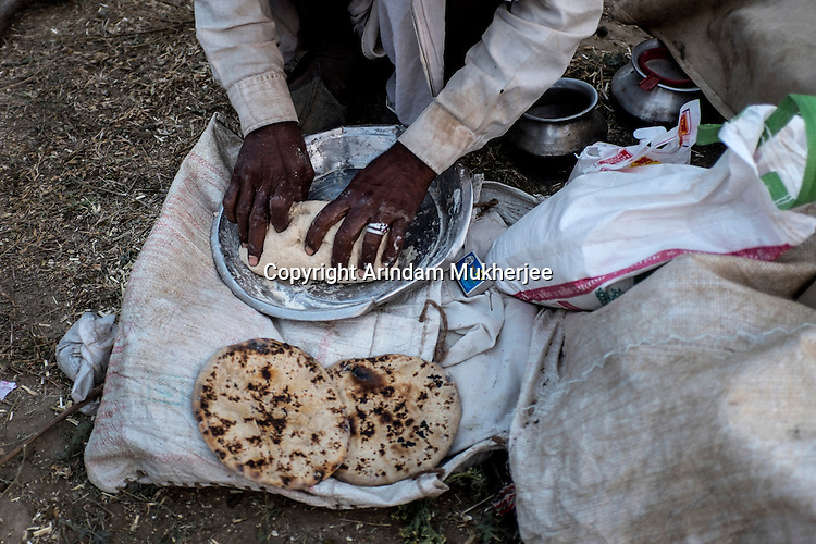 A man making Indian bread (roti) at Pushkar fair ground. Rajasthan, India.