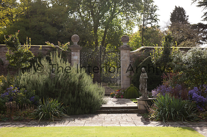 A statue in the garden has become engulfed by a plant in one of the flowerbeds