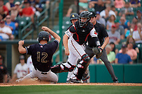 Rochester Red Wings catcher Wynston Sawyer (16) looks for a throw as Mike Tauchman (12) slides home safely during an International League game against the Scranton/Wilkes-Barre RailRiders on June 24, 2019 at Frontier Field in Rochester, New York.  Rochester defeated Scranton 8-6.  (Mike Janes/Four Seam Images)