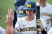 Michigan Wolverines shortstop Benjamin Sems (2) celebrates with his teammates after scoring against the Ohio State Buckeyes on April 9, 2021 in NCAA baseball action at Ray Fisher Stadium in Ann Arbor, Michigan. Ohio State beat the Wolverines 7-4. (Andrew Woolley/Four Seam Images)
