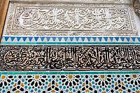 Fes, Morocco.  Attarine Medersa, 14th. Century, Fes El-Bali.  Arabic Calligraphy in Stucco and Tile,  Geometric Tile Work Underneath.