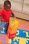 12 month old baby boy standing playing with toys standing in front of stack of blocks putting zebra animal toy on top concept on top of vertical