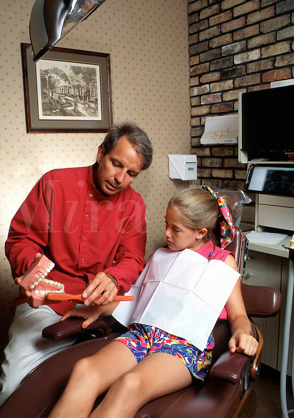 A dentist demonstrates proper tooth brushing technique to his young female patient.