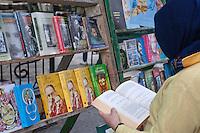 Cuba, Havana.  Booksellers, Plaza de Armas.  Potential Customer Examining a Work.