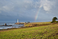 A rainbow's arc disappears into the clouds next to the Pigeon Point Lighthouse at Pigeon Point Lightstation State Historic Park along the California coast.