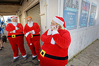 Pictured: Three men dressed as Santas wait before the swim. Wednesday 25 December 2019<br /> Re: Hundreds of people in fancy dress, have taken part in this year's Porthcawl Christmas Swim in south Wales, UK.