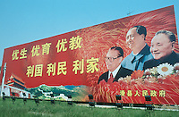 China. Province of Henan. Hua Xian town. A large poster on the road with the pictures of three important communist chinese leaders: Deng Xiaoping (right), Mao Zedong (middle), Jiang Zemin (left). The words and the message say: Healthy birth, well feeded and trained, good education. Good to the country, for its people and for the chinese families. © 2004 Didier Ruef