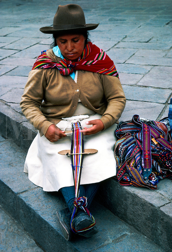 Peruvian woman sitting on steps weaving a belt or strap on a small loom.