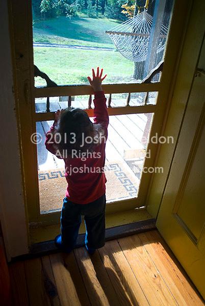 Baby boy looking through screen door, reaching up