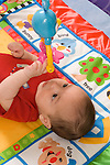 3 month old baby boy on back closeup reaching to touch or grasp hanging toys lying on activity mat vertical
