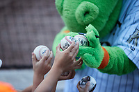 """Charlotte Knights mascot """"Homer the Dragon"""" signs autographs for young fans during the game against the Nashville Sounds at Truist Field on June 4, 2021 in Charlotte, North Carolina. (Brian Westerholt/Four Seam Images)"""