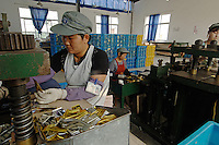 Female metal pressing machine operators at one of the worlds most successful brush manufacturers in the world. The Yixing Zhenxin Made Brush Co. Ltd produces a staggering 220,000 brushes every day using relatively non-high-tech but labour intensive methods for a variety of domestic and international clients. International clients include the home Depot, Wallmart and ICI to name a few..