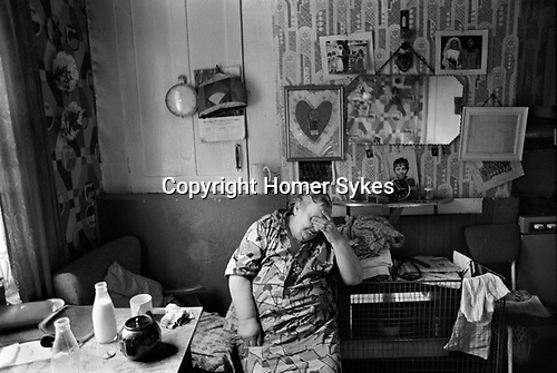 Whitechapel, London. 1975<br /> Great Eastern Buildings Peabody Housing Estate.  A resident (Mrs Edna Clarke?) in her living room covers her eyes, head in hand, exhausted after a hard days work. She is wearing a typical 1970's housecoat, an overall that covered her best clothes and was often worn rather than an apron for housework. Yesterdays empty glass pint milk bottle and todays fresh pinta stand on the crowded table while the tea brews. On the walls of her room are photographs of her daughters wedding and a large lace heart shaped decoration, reminding her that she is always loved. These were commonly sent back to mothers and grandmothers by soldiers stationed in Germany at the time.<br /> <br /> These crumbling blocks of flats were beginning to be torn down during the mid 1970's. (Lace heart info supplied by Mark Hill. Thanks you.) This woman was Mrs Edna Clarke?