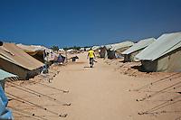 Tunisie RasDjir Camp UNHCR de refugies libyens a la frontiere entre Tunisie et Libye ....Tunisia Rasdjir UNHCR refugees camp  Tunisian and Libyan border  Campo profughi alla frontiera libica Uomo con maglia gialla cammina in mezzo alle tende Man walking beside tents