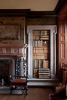 The fireplace in the hall is wood painted to look like stone. Game books are shelved alongside