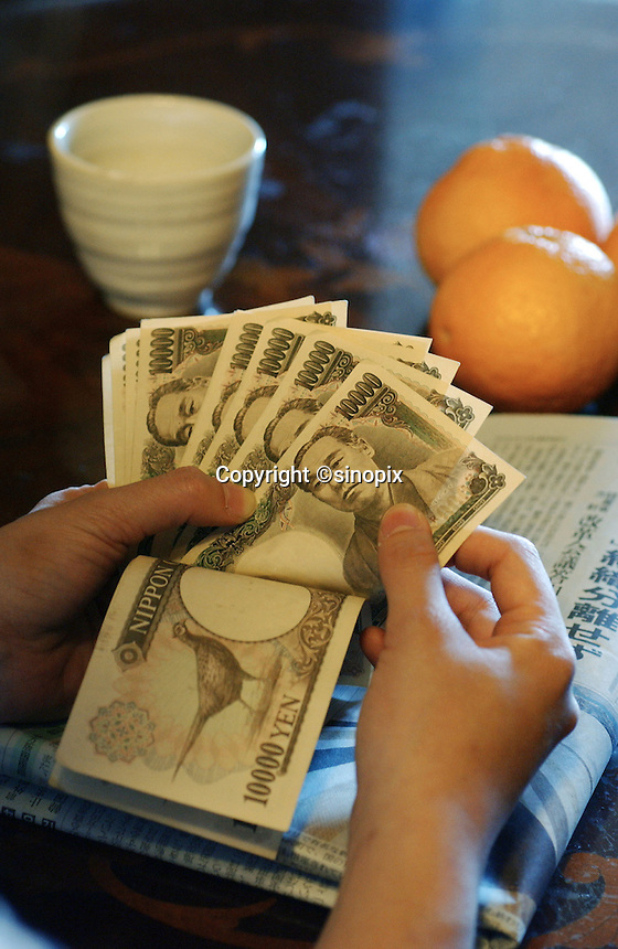 Japanese Yen is counted at a table in a Tokyo household.  As the recession bites and the Japanese economy shrinks times are getting harder for Japanese.