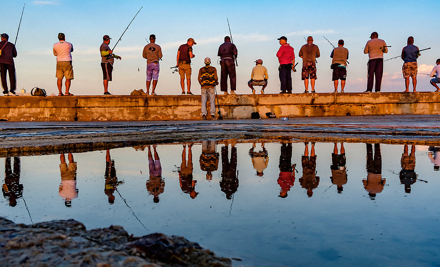 Fourteen fishermen perch on The Malecon sea wall in Havana Harbor angling for day's catch, with a large puddle acting as a mirror.
