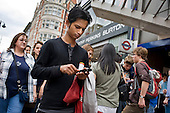 Man using a mobile phone, Oxford Street, London.