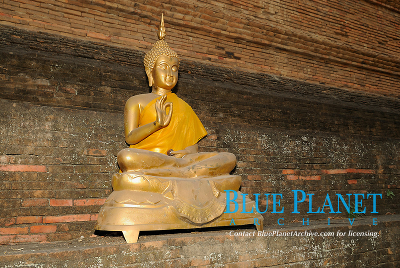 Sitting Buddha covered with gold in a Buddhist temple in Chiang Mai city, Thailand, Southeast Asia. Buddha may be pictured in number of different poses. f the right hand is raised, palm outwards, this indicates that Buddha is imploring peace.