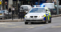 Silver 5 series BMW estate Metropolitan Police car on emergency call driving through heavy traffic, London UK..