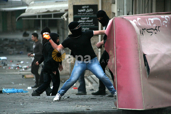 A Palestinian man throws a molotov cocktail at Israeli soldiers during clashes in the West Bank city of Hebron, 13 March 2013, following the funeral of Mahmoud Adel al-Titi, 22, who was shot dead by an Israeli soldier during an Israeli military operation in al-Fawwar refugee camp on Tuesday. Photo by Mamoun Wazwaz