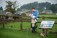 """A mother breastfeeding her baby of eight months at a visitor farm park with cows in the background.<br /> <br /> Image from the breastfeeding collection of the """"We Do It In Public"""" documentary photography picture library project: <br />  www.breastfeedinginpublic.co.uk<br /> <br /> <br /> Gloucestershire, England, UK<br /> 30/09/2013<br /> <br /> © Paul Carter / wdiip.co.uk"""