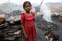 INDIA Jharkhand Dhanbad Jharia, children collect coal from coalfield to sell as coking coal on the market for the livelihood of her family, 8 years old girl Sonia / INDIEN Jharia, Kinder sammeln Kohle am Rande eines Kohletagebaus zum Verkauf als Koks auf dem Markt , Maedchen Sonia 8 Jahre verkokst die gesammelte Kohle, Hintergrund brennende Kohlefloeze