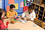 Educaton preschool 4-5 year olds table activities manipulatives two girls and a boy playing separately at table with stringing cards and puzzle horizontal