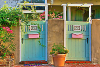Green gates with pink mailboxes surrounded by pink and yellow flowers in St. Augustine, Florid