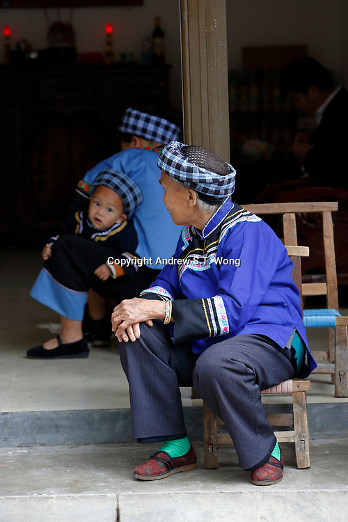 An elderly woman of the ethnic Bouyei Tribe looks at a young boy at Wangmo County in China's southwestern Guizhou Province, April 2019.