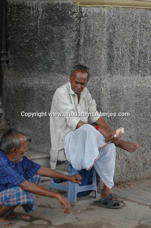 A money changer waits at a foot path for customers with bundles of notes. He charges Rs 5 to change a Rs. 100.00 note to a smaller dinominations. Kolkata, West Bengal,  India  7/18/2007.  Arindam Mukherjee/Landov