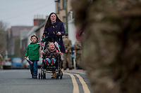 Wednesday 26 March 2014<br /> Pictured: A mum walks through the soldiers to support the troops<br /> Re: 236 Signal Squadron ( part of 14 Signal regiment who are based at Cawdor Barracks in Brawdy Parade through the streets of  St.Davids Pembrokeshire led by Haverfordwest Air Training Corps Band and are then Presented with medals