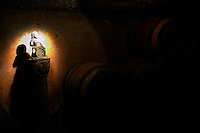 A statue on a piedestal in the underground cellar at Guigal showing a small bacchus sitting on a wine barrel holding a grape bunch in his hand.  Domaine E Guigal, Ampuis, Cote Rotie, Rhone, France, Europe
