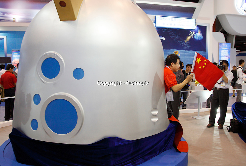 A Chinese TV presenter walks out of a model of the Shengzhou VII landing craft at the 2008 China International Aerospace and Aviation Exhibition in Zhuhai, China..