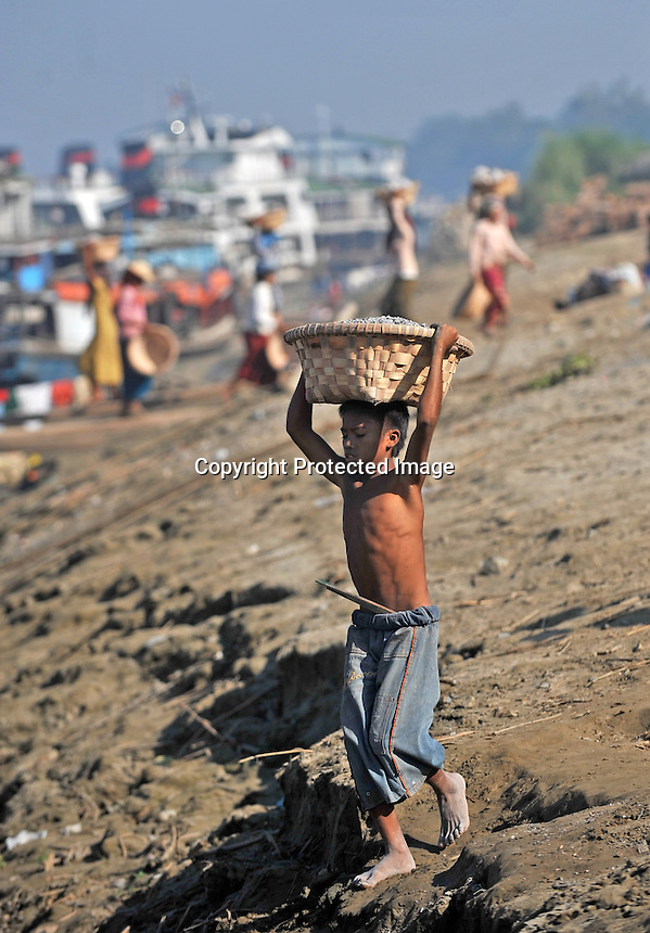 Children carry stones onto a barge on the outskirts of Mandalay, Burma November 08.  Child labour is a normal in Burma.<br />