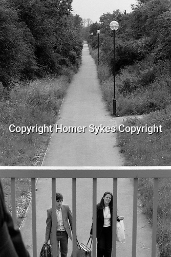 Milton Keynes couple walking back from the shops with shopping bag. Milton Keynes was known for creating green walkways allowing residents to walk to the shops and not along a busy road. Buckinghamshire 1977. 1970s