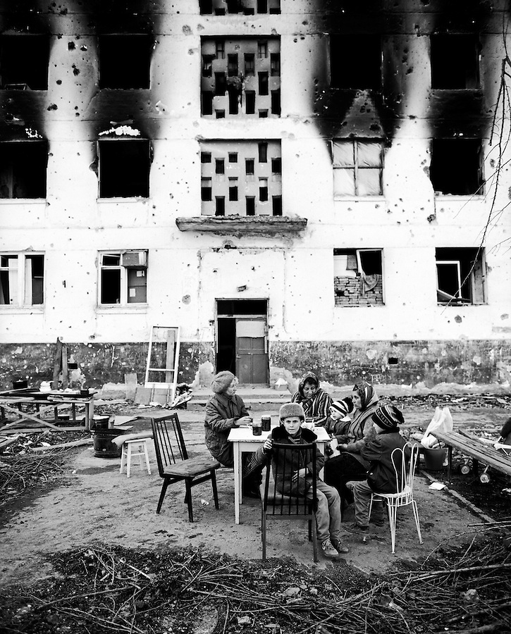 Grozny, Chechnya, March 1995..A family eat lunch outside their ruined apartment block in the city centre after rebel forces retreated from the city in the face of the Russian bombardment.