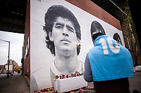 NEW YORK, UNITED STATES - NOVEMBER 25: A fan holds a T-shirt as Flowers are placed by a Mural of Diego Maradona on November 25 2020 in New York. The Argentine soccer legend died at the age of 60, his spokesman announced(Photo by Eduardo Munoz/VIEWpress via Getty Images)