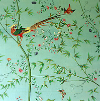 A brightly coloured bird sits on a bamboo branch and butterfly flutters amongst the flowers in this hand-painted Chinese wallpaper which dates from the 1830s