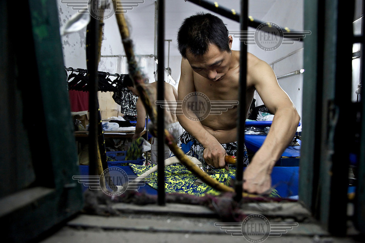 Rural migrants work in a garment sweatshop on the outskirts of the southwestern Chinese megapolis of Chongqing. They often work through the nights, earning 1,000 - 6,000 yuan per month depending on work load, a decent income compared with subsistence farming. For many, this is a long and arduous step in the transition from farming to urban living. China is hoping by relocating farmers into cities they would start to buy food, making a break from the cycle of farmers consuming only what they produce. The Chinese government plans to move 250 million rural residents into urban areas over the coming dozen years though it is unclear whether people want to move and where the money for this project will come from. Further urbanisation is meant to drive up consumption to counterbalance an export orientated economy and end subsistence farming but the drive to get people off the land is causing tens of thousands of protests each year. /Felix Features