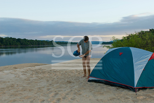 Pará State, Brazil. Xingu River. Patrick Cunningham in camp, pouring water.