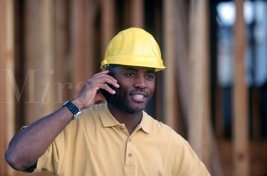 Architect talks on mobile phone while checking construction site