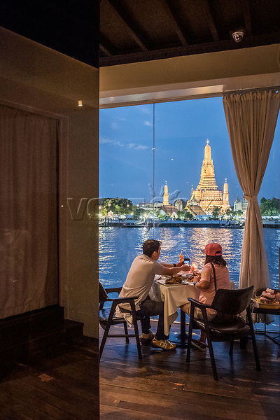 Thailand, Bangkok. Blick von Hotel Sala Rattanakosin auf Wat Arun, Mae Nam Chao Phraya Fluss, Gewaesser, Tempelanlage, Buddhismus, buddhistischer Tempel, Wat Arun Ratchawararam Ratchawaramahawihan, Abend, Blaue Stunde, Ausgehen, Ausblick, Stadtansicht, Menschen, innen, Asien, Suedostasien, Thai, Reise, Travel. Engl.: Thailand, Bangkok. view from Sala Rattanakosin hotel towards Wat Arun Ratchawararam Ratchawaramahawihan, buddhism, buddhist temple, Mae Nam Chao Phraya river, evening, blue hour, restaurant, Asia, Southeast Asia, Asian, travel