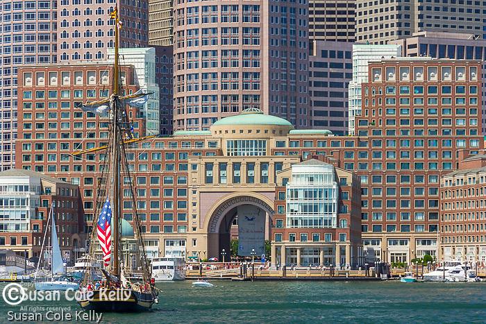 The Pride of Baltimore II sails under the Boston financial district on Boston Harbor, Boston, Massachusetts, USA