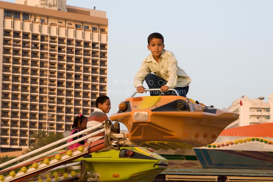 Tripoli, Libya, North Africa - Children on Amusement Park Ride.  Boy Standing without Seat Belt.