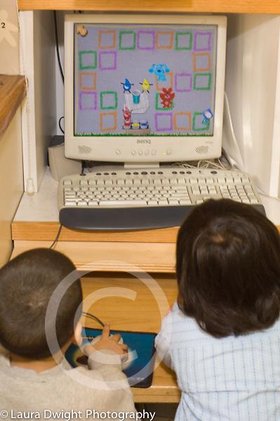 Preschool Headstart 4 year olds two children using computer in classroom