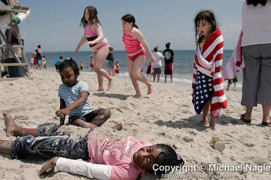WANTAGH, NY -- MAY 28, 2005: Nia Hood, 4, covers her sister Nydja, 8, with sand as Grace, 6, (R) looks on during the New York Airshow at Jones Beach May 28, 2005 in Wantagh, New York. (PHOTOGRAPH BY MICHAEL NAGLE)