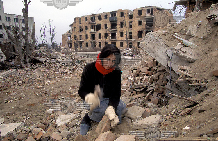 ©ÊHeidi Bradner / Panos Pictures..A Chechen woman salvages bricks from the rubble of Grozny to sell or use as building material in a city which is devastated. ..Grozny, Chechnya.