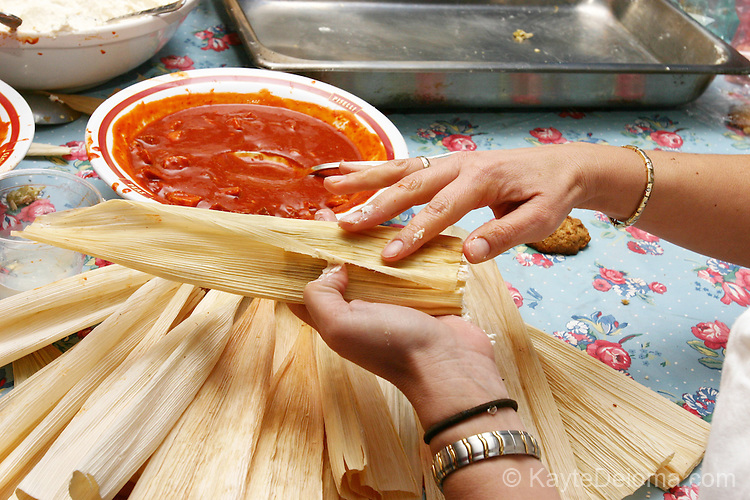 Hands making a red chili tamal at a family Tamalada (tamale making party), Torrance, CA