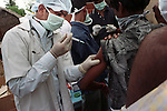 A doctor, in a Government immunisation camp, works quickly to prevent the outbreak of disease.Tamil Nadu. India.